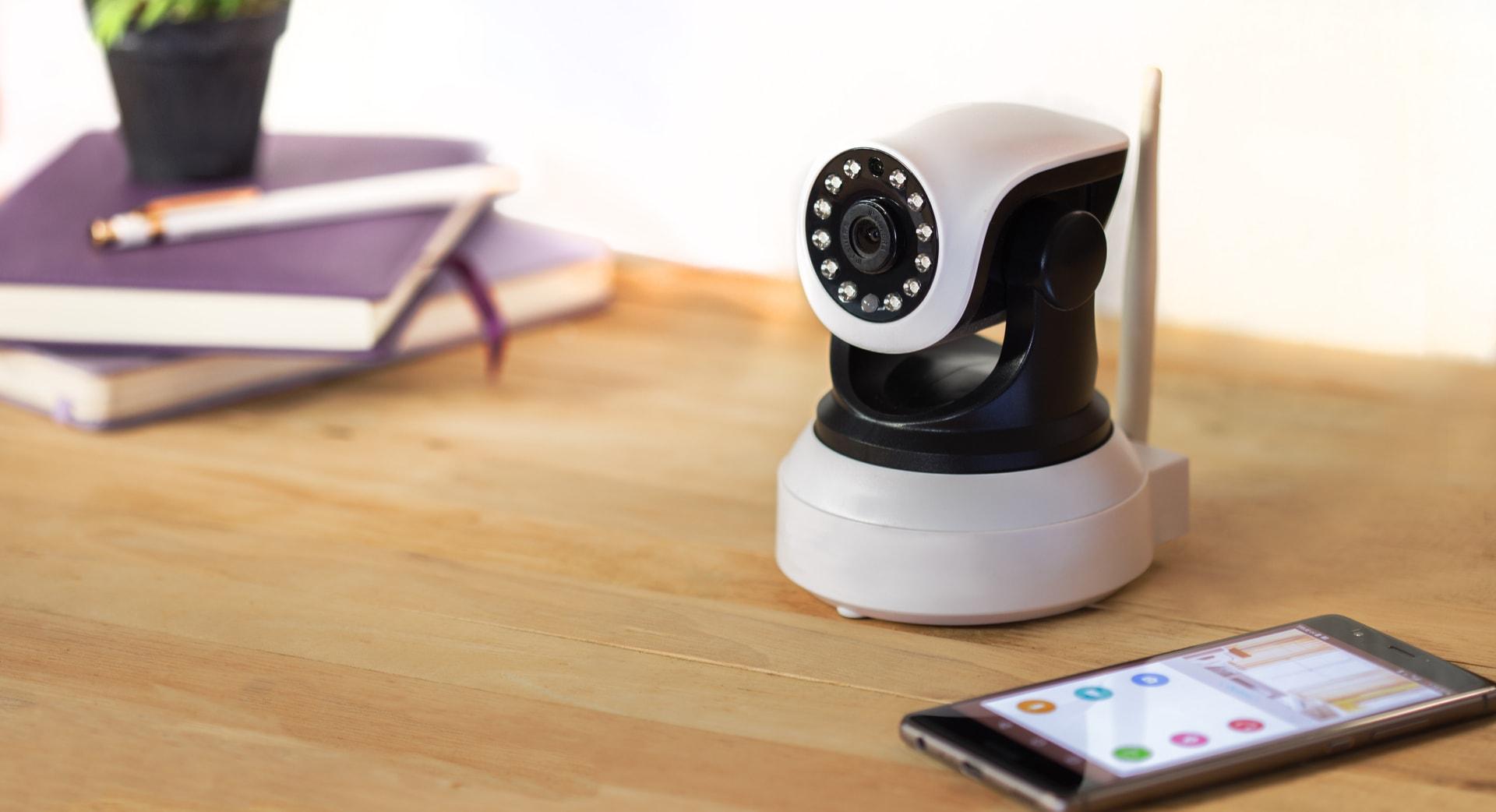 Camera op houten tafel naast smartphone voor camerabewaking via internet van GW Security Group