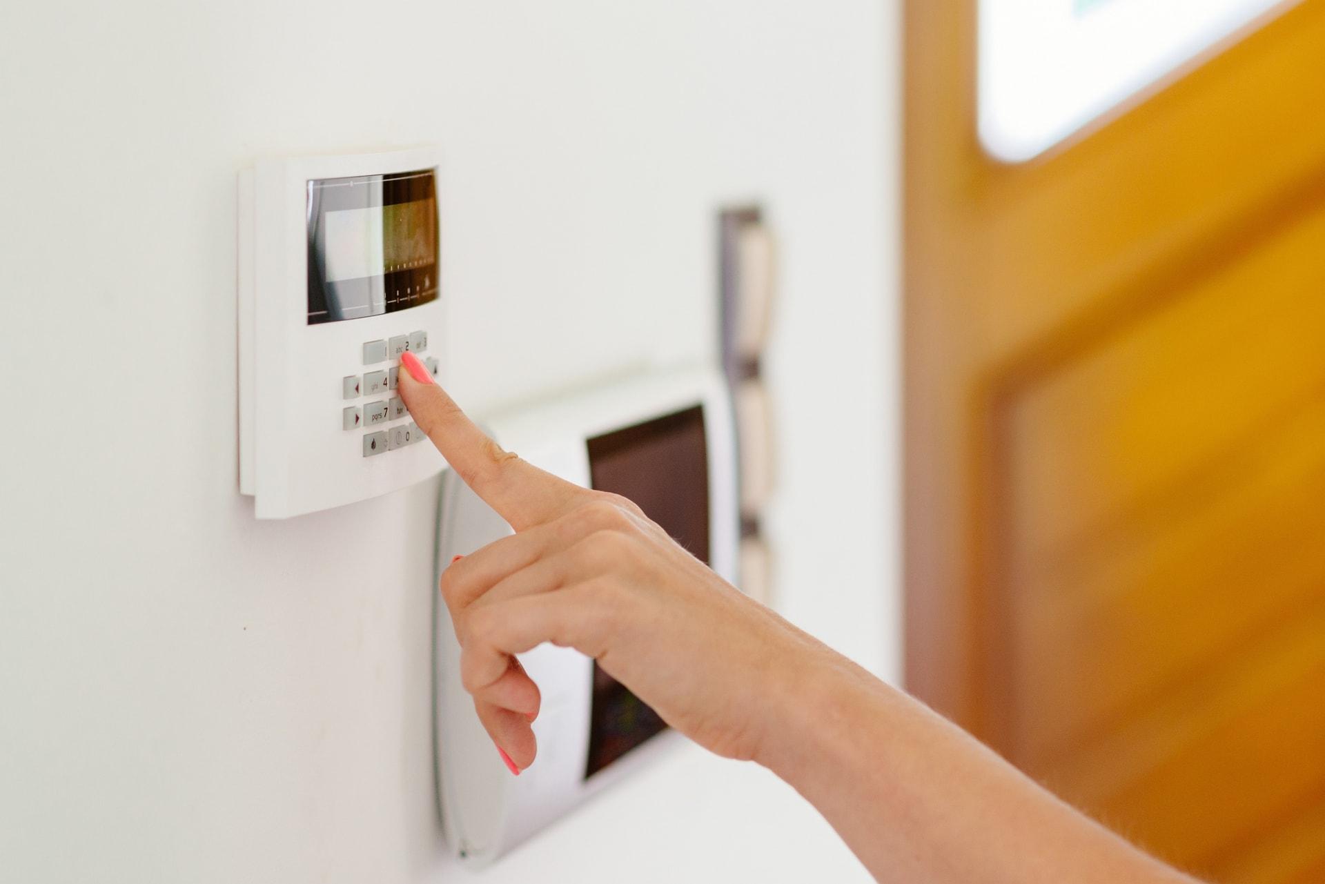 Vrouw tikt de code in van haar systeem voor huisbeveiliging van GW Security Group