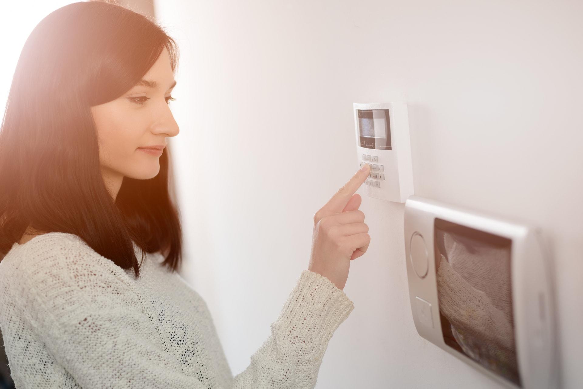 Jonge vrouw geeft alarmcode in naast videofonie in een geïntegreerd systeem van GW Security Group