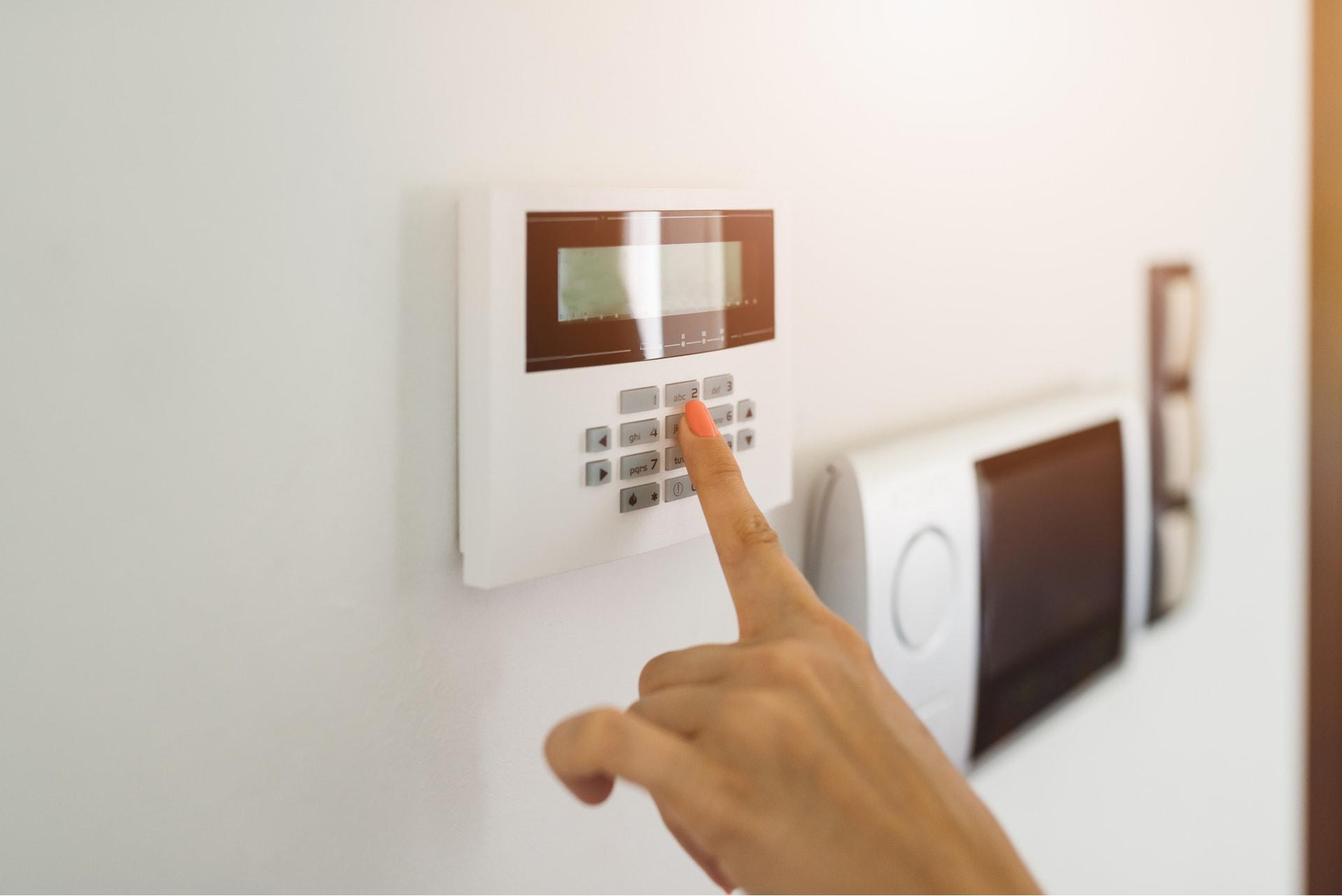 Jonge vrouw tikt code in het alarmsysteem in haar woning van GW Security Group