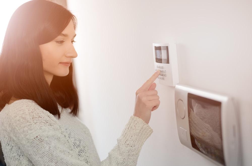 Jonge vrouw typt code in Risco-alarmsysteem van GW Security Grou