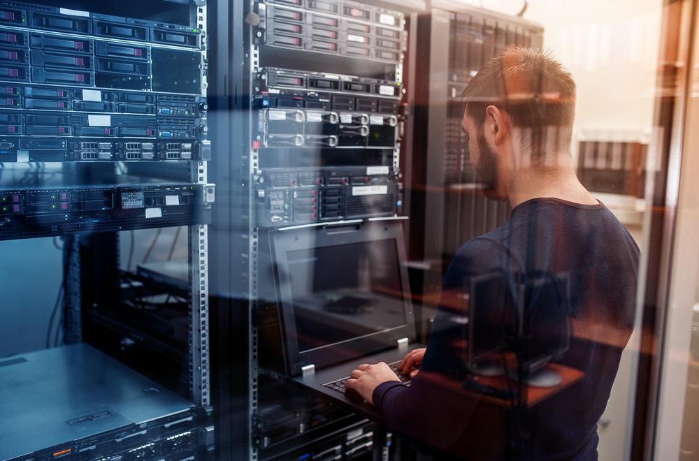 Jonge man update het netwerk van reservesystemen in de meldkamer van GW Security Group
