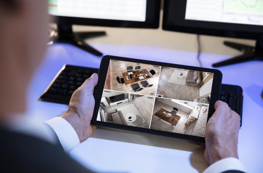 Zakenman bekijkt beelden van zijn totaalbeveiliging thuis en op kantoor dankzij GW Security Group